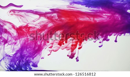 Blue, purple, pink and red ink in water - stock photo