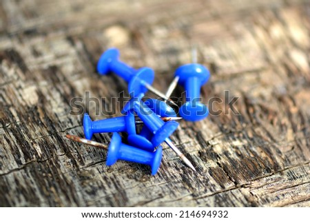 blue push pins on old wooden background - stock photo