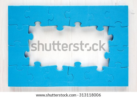 Blue puzzle frame on white wooden background - stock photo