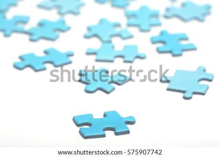 Blue puzzle pieces on a white surface. Focus point on the first piece in front. Abstract and decorative.