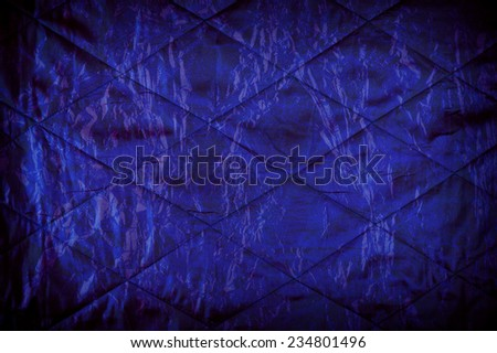 Blue quilted texture abstract with black vignette, material crumpled surface background in horizontal orientation, digitally altered, nobody. - stock photo
