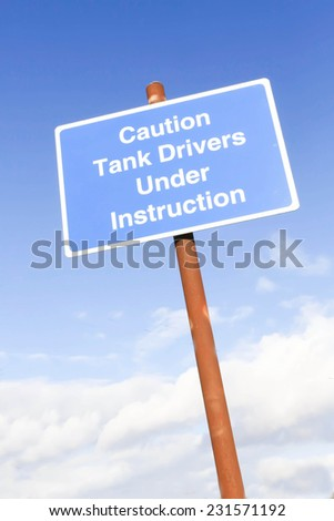 Blue rectangular warning road sign indicating tanks are being driven by drivers under instruction ahead.