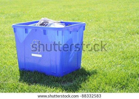 blue recycling box on grass garbage day waiting to be picked up - stock photo