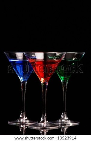 Blue, red, and green cocktails on black background - stock photo