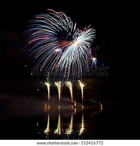 Blue, Red and Green Fireworks reflected in a murky lake - stock photo