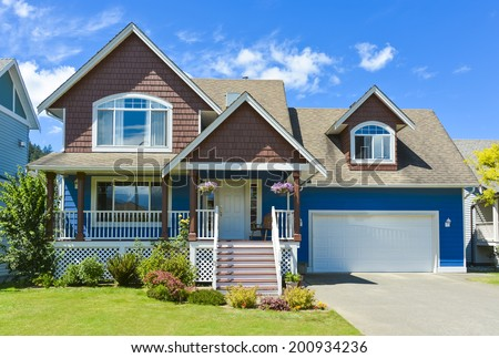 Blue residential house with concrete driveway in front and blue sky background. - stock photo