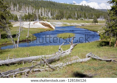 Blue river meandering through smoke and steaming water coming out of  hot springs and geysers  in Yellowstone National Park, Montana, Wyoming, USA - stock photo