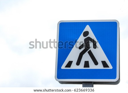 blue road sign of a pedestrian crossing