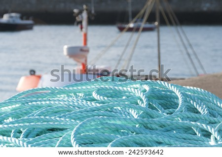Blue ropes coiled by the harbour - stock photo