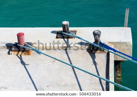 Blue Ropes on Red and Black Bollards on concrete pier