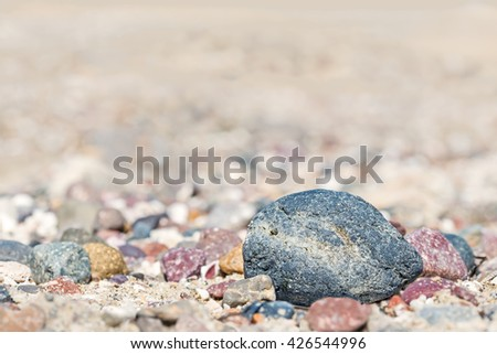 Blue rough texture rock on sand with group of colorful stones. Shallow depth of field. Low angle view. Heavily blurred background. Selective focus on foreground rock. Copy space.  - stock photo