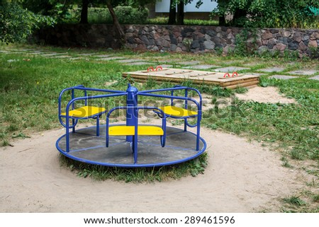 Blue roundabout with yellow chairs in empty child playground - stock photo