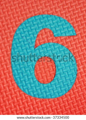 Blue rubber number 6 on red rubber background with tread plate texture - stock photo