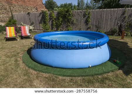 blue rubber pool on the grass for children, 2 lawn chairs in the back - stock photo