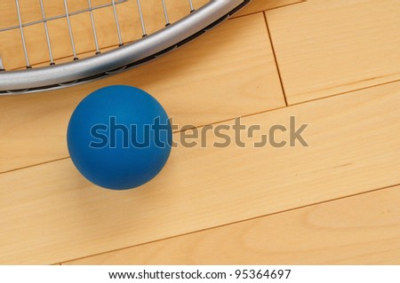 Blue Rubber Racquetball and Racquet on Hardwood Court Floor - stock photo