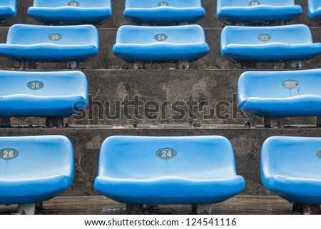 blue rubber seats in a sport stadium in the out door under rain, with a missing seat