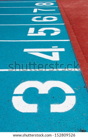 Blue running track at the stadium with white lines - stock photo