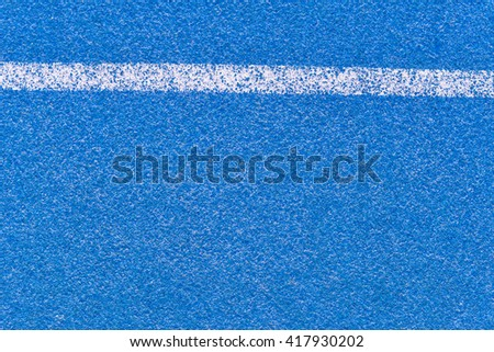 Blue running track rubber cover with white line - stock photo
