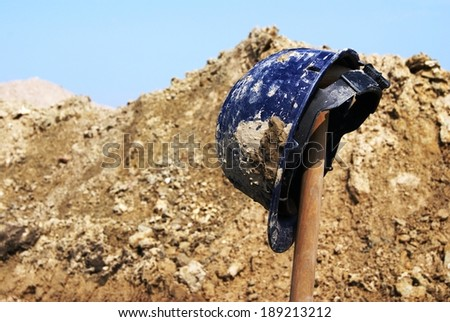 Blue safety hard hat on top of a spade at an archaeological excavation. Pile of dirt and stroke of blue sky in the background.  - stock photo