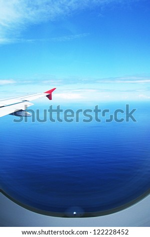 Blue sea and sky from the window of airplane - stock photo