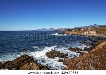 Blue sea and sky, waves breaking off shore, and beautiful homes, at the Fiscalini Ranch Preserve on the Big Sur coast, California Central Coast, near Cambria CA. - stock photo