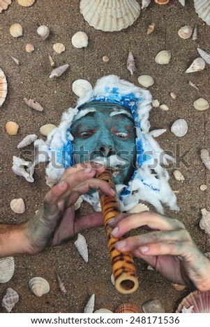 Blue sea man playing flute underwater - stock photo