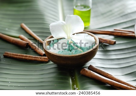 Blue sea salt ,flower in wooden bowl. oil with cinnamon on banana leaf - stock photo