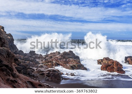 Blue sea & sky, white clouds, waves splashing on huge rocks, offshore, along a rocky coastline, aquamarine surf, white caps, traveling the Big Sur Highway (Highway 1) on the California Central Coast. - stock photo