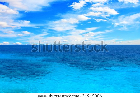 blue sea under azure sky on hot summer day - stock photo