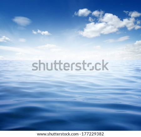 Blue sea water surface on sky - stock photo