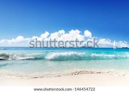 Blue sea, white sund and yachtes on beach. Seychelles island.  - stock photo