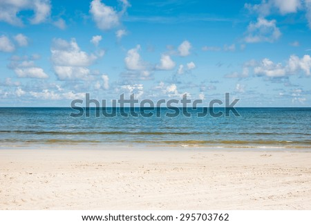Blue sea with blue sky and white sand beach - stock photo