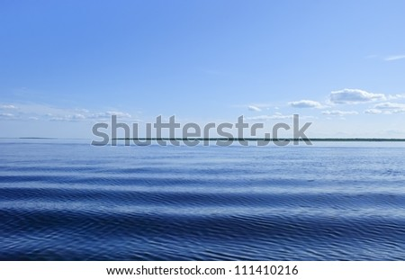 Blue sea with waves and blue sky with clouds - stock photo