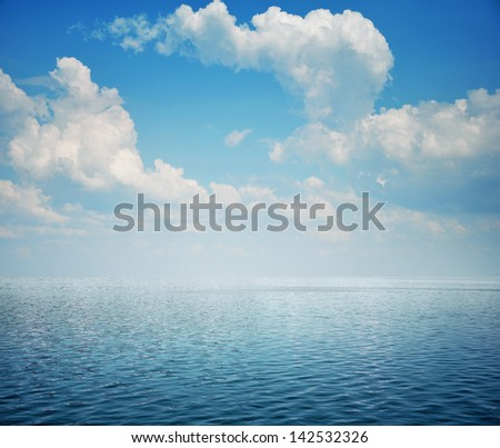 Blue sea with waves and sky with airy clouds - stock photo