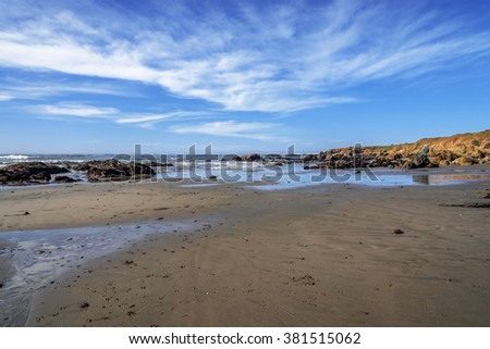 Blue seas & skies, white clouds, shimmering & reflective tidal pools, rock and unusual geological formations, along the rugged Big Sur coastline, near Monterey, CA. on the California Central Coast. - stock photo