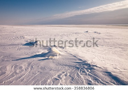 Blue shadows and wind patterns on thick snow at frozen Ladoga lake near St. Petersburg city, Russia - stock photo