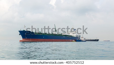 Blue ship is bunkering by small craft in the open sea - stock photo