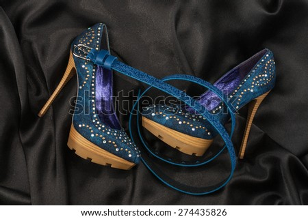 Blue shoes and belt  lying on black satin, as background - stock photo
