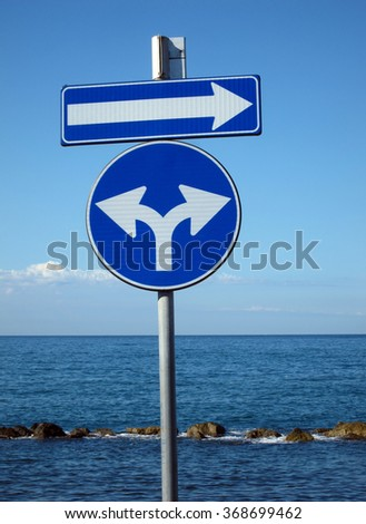 blue signs for directions on background with sea and sky - stock photo