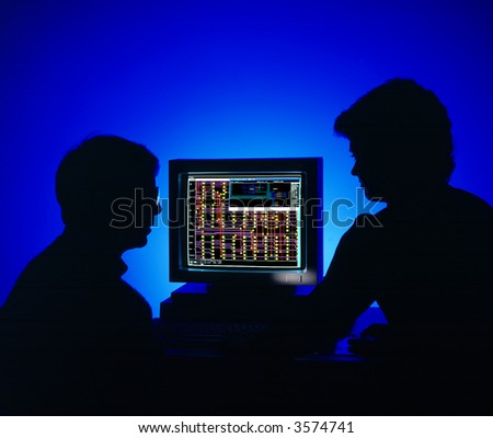 Blue silhouetted man and woman gazing at a CADCAM design on monitor - stock photo