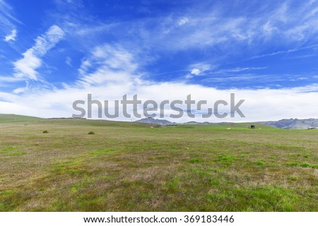 Blue skies, white clouds, green grass, & open range land dominate the landscape, near Hearst Castle, traveling the Big Sur Highway (Highway 1), on the California Central Coast, near Cambria, CA. - stock photo