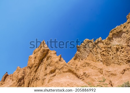 Blue sky above canyon of red clay - stock photo