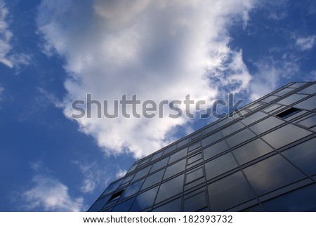 Blue sky and beautiful white clouds reflected on a big, glass building