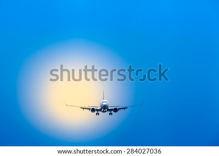 Blue sky and blurred yellow light with an airplane on landing approach in front of it/Air Travel - Plane at Landing Approach  - stock photo