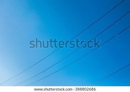 Blue sky and energy cables at sunny day.