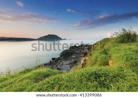 Blue sky and green grass during sunrise at Tanjung Ann, Lombok, Indonesia. The image may has blurred effect and soft focus due to long exposure.