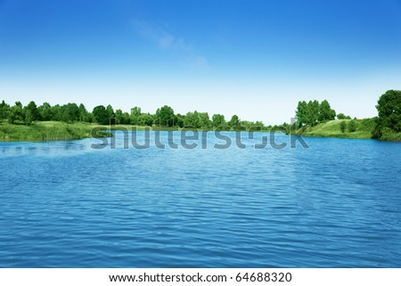 Blue sky and green trees over lake. - stock photo