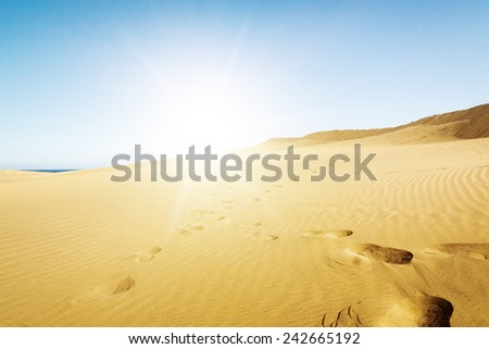 Blue sky and sand dunes with footprints. Canary islands, Maspalomas. Spain.  - stock photo