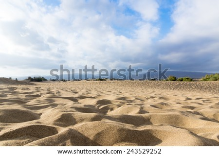 Blue sky and sand dunes with footprints. Canary islands, Maspalomas. The mountains in the background.