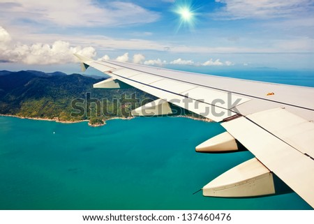 Blue sky and sun view over the wing of the plane. - stock photo